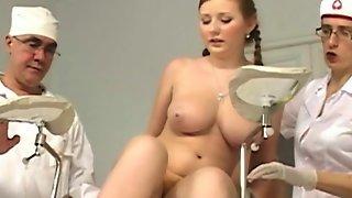 Опытные доктора осматривают обнаженную красотку с большими дойками