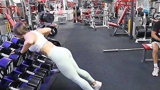 Спортивная баба в тренажерном зале позирует в обтягивающей одежде