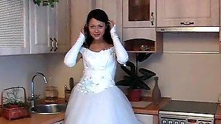 Телка в свадебном платье ласкает пизду вибратором на кухне