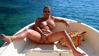 Голая баба в лодке показывает большие сиськи