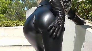 Блондинка в черном костюме из латекса светит упругой попкой на улице