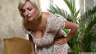 Белокурая женщина в платье и с большими дойками ласкает соски пылесосом