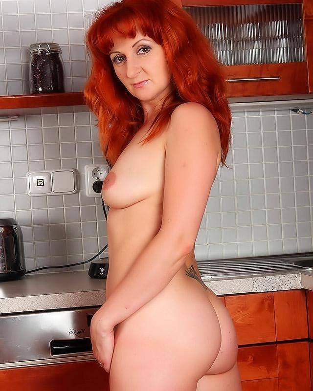 Рыжая мамка на кухне выставила напоказ свою волосатую вульву