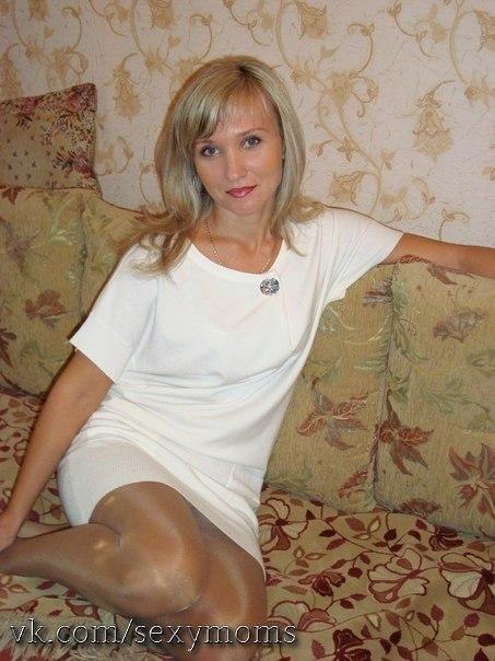 Сидя на кровати модель раздвигает ножки в гольфах секс фото