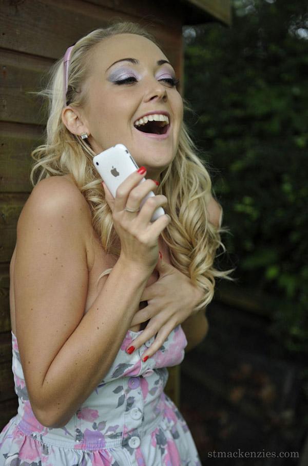 Блондинка стоит за сараем и занимается сексом по телефону