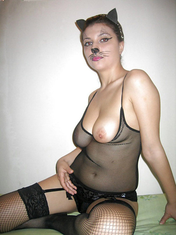 Женщина-кошка в прозрачном белье сидит на кровати