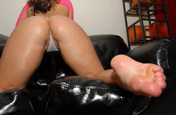Развратная кудряшка на черном диване страстно позирует