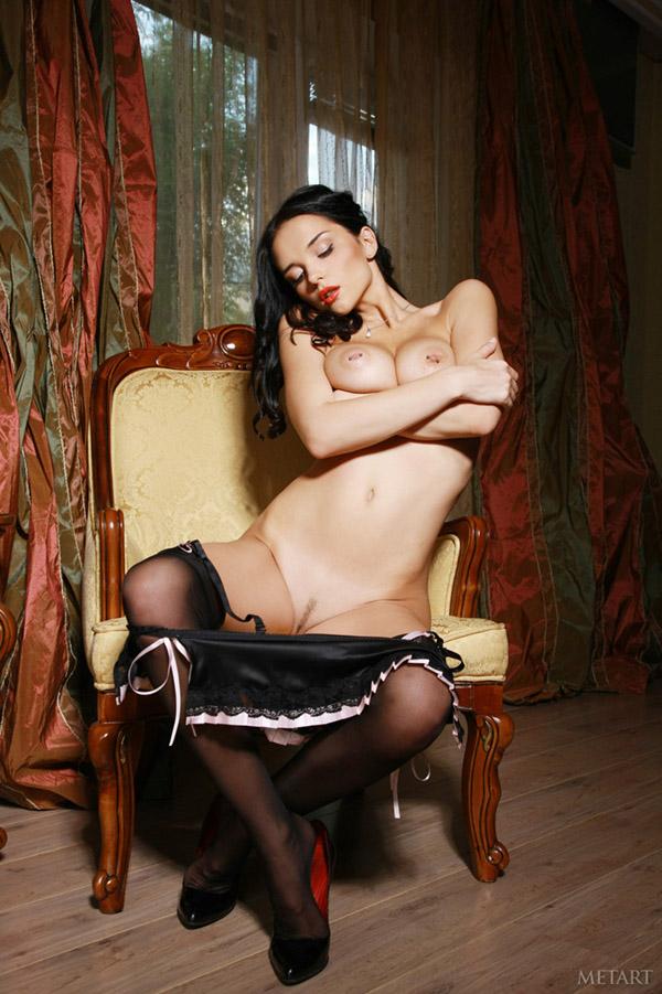 Модель с темными волосами в чёрных гетрах сидя на стуле оголяет пирсингованные соски