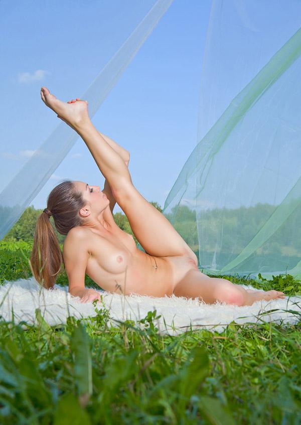Молоденькая гимнастка упражняется в саду
