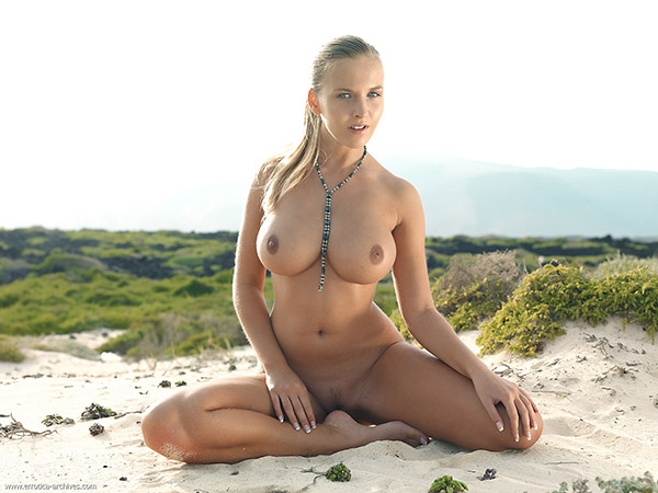 Конопатая фея совершенно обнаженная сидит на пляже