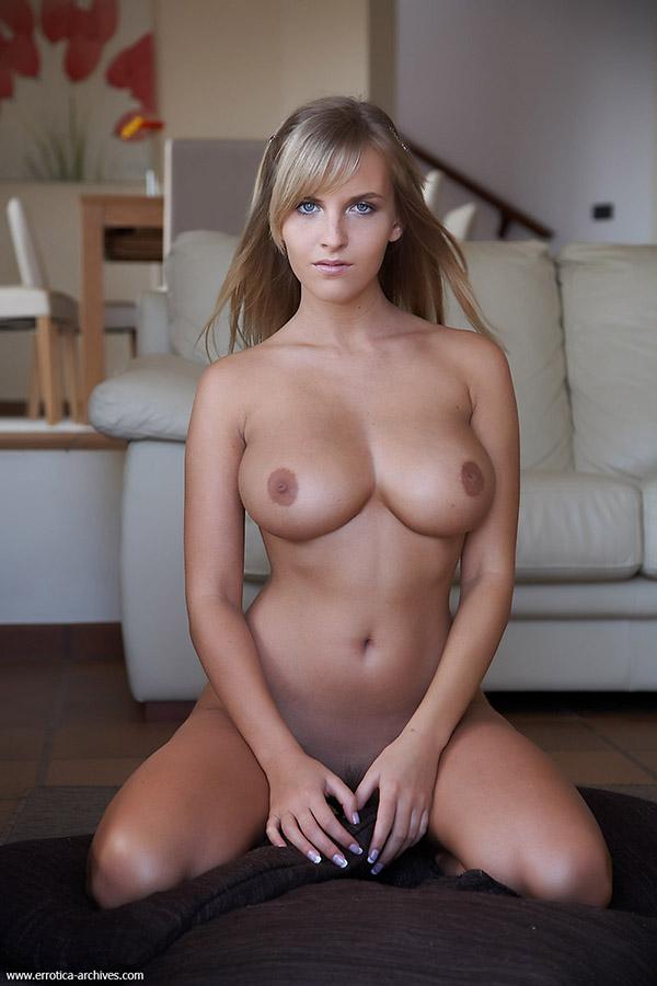 Красотка светит большими дойками сидя на полу