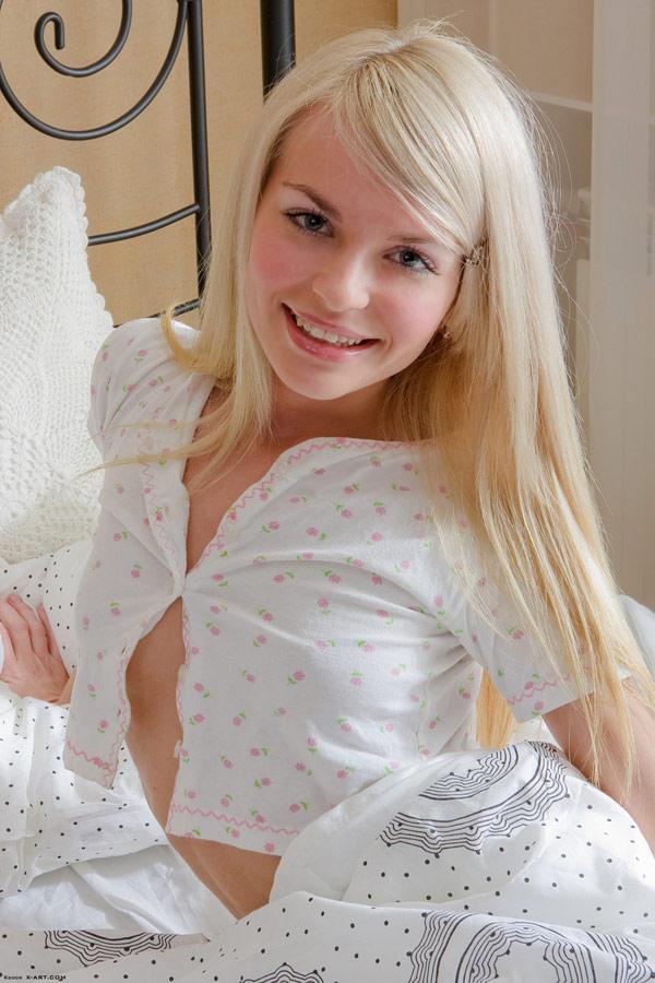 Красивая блондинка спускает пижаму не поднимаясь с койке