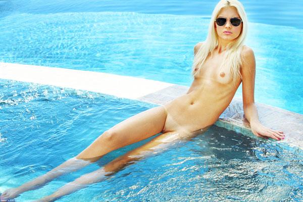 Тощая блонда купается в бассейне без купальника