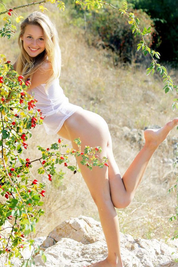 Молодая красотка раздевается стоя у куста шиповника