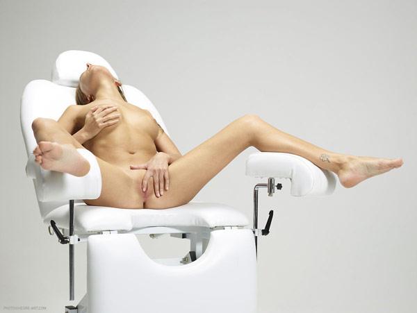 Обнаженная фрау массирует себя на гинекологическом кресле