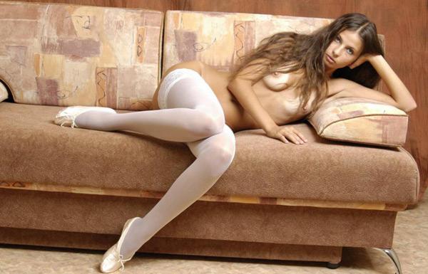 Расселась в белых чулках на бежевом диване
