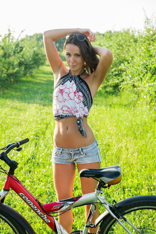 Спортивная мастерица заехала в зеленый сад на велосипеде