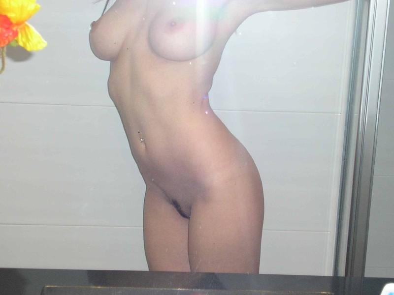 Совершеннолетняя голая модель с темными волосами позирует на камеру