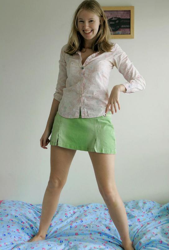 Сидя на кроватке сбросила блузку и юбочке