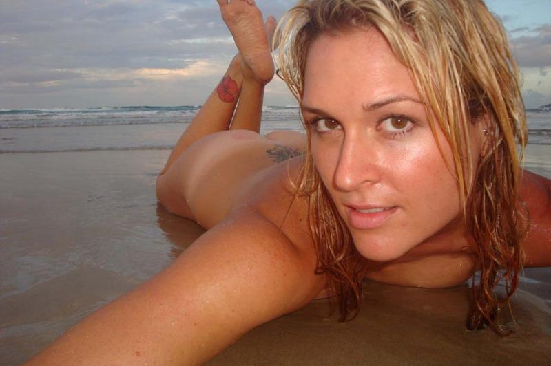 Шалунья лежит спиной на пляже во время заката