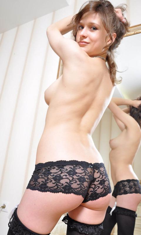 Сексуальная подружка сидит в постели в одних чулках