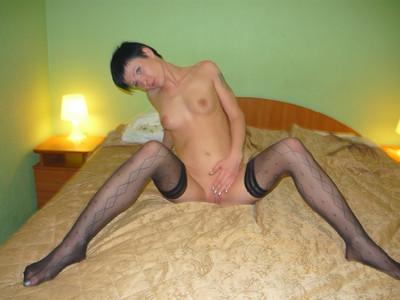 Ухоженная темноволосая девка в носках нагишом зажигает на кроватке