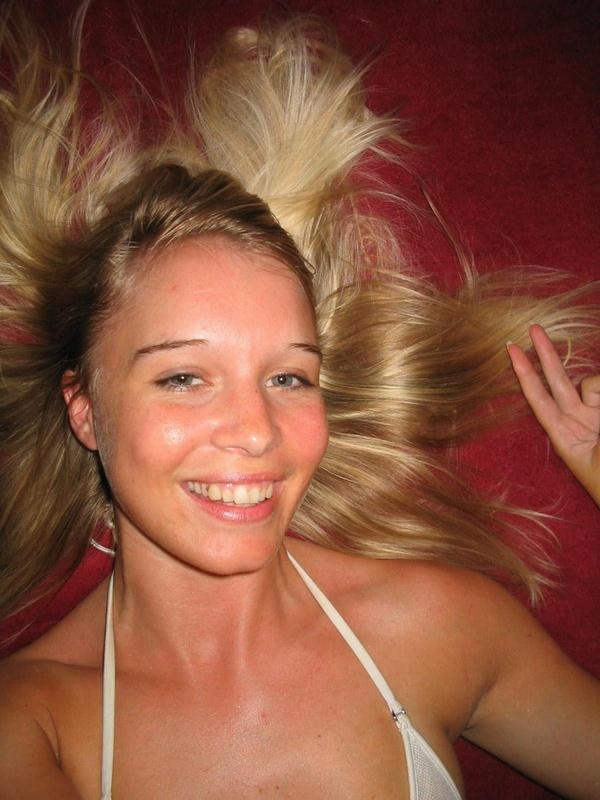 Молодая модель со свелыми волосами расположилась на красной постели секс фото