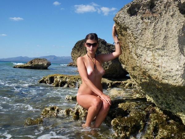 Во время отпуска блядь позирует на пляже без лифчика