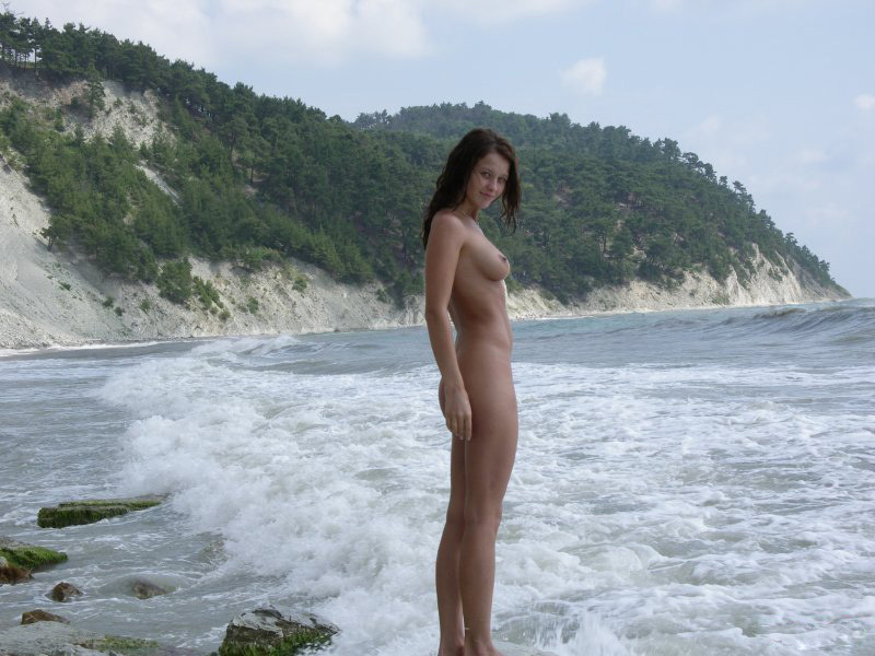 Голая чика наслаждается прибоем на берегу