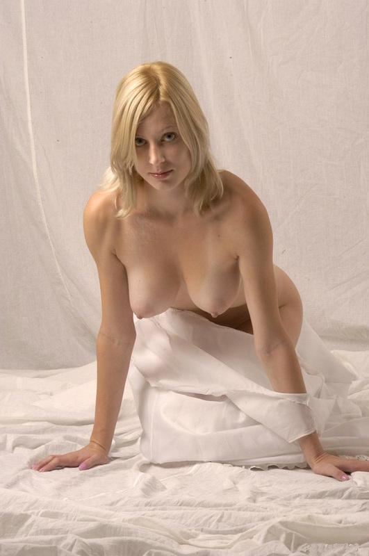 Красотка на белых простынях показывает свои буфера
