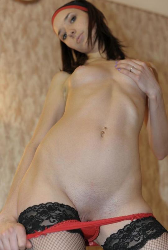 Сексуальная нимфа позирует на постели в красивых чулочках