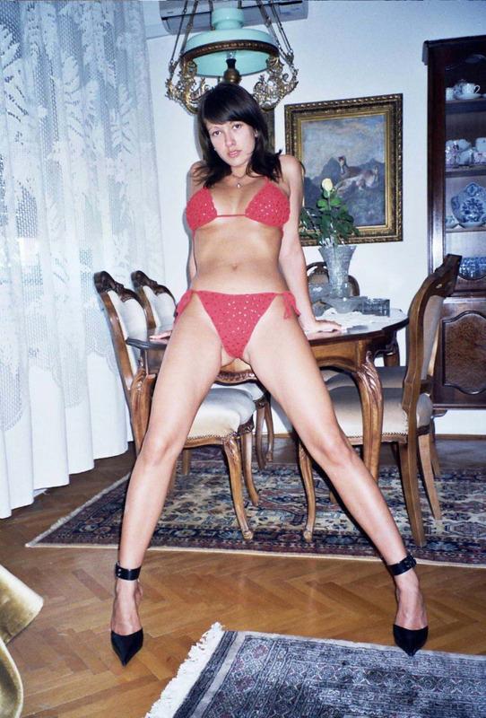 Брюнетка намерена посреди комнаты снять с себя красные трусы