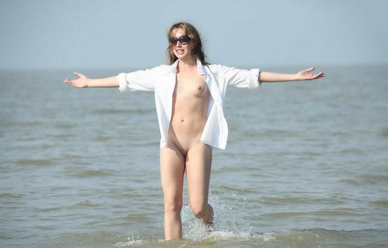 Барышня развлекается без одежды на песке летом