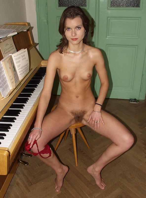Учительница музыки сидит с расставленными ножками недалеко от пианино