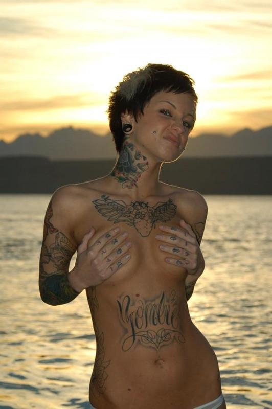 Татуированная неформалка позирует на берегу водоема