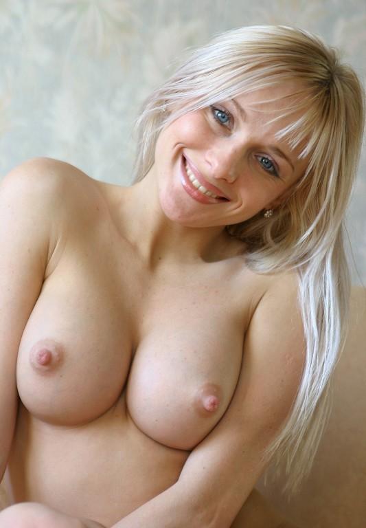 На белом диване блондиночка светит обнаженными прелестями