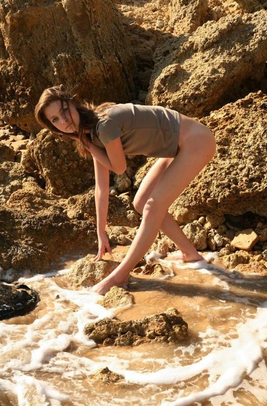 Woman в красном купальнике шалит среди песка