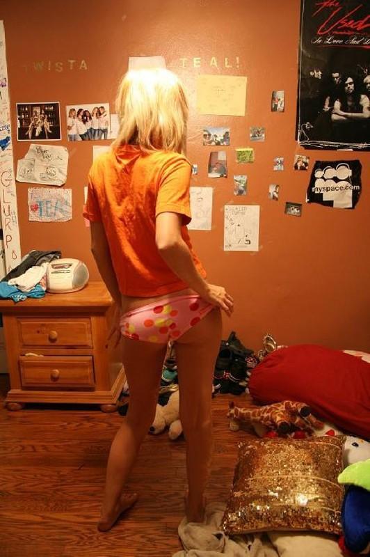 Сексуальная блонди стоит на кровати лишь в бикини
