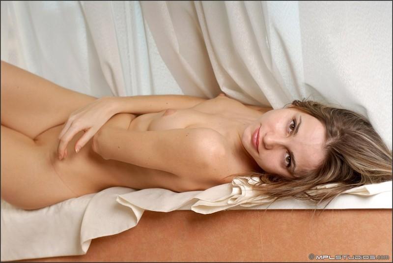 Нагая Анжелина сидит на подоконнике