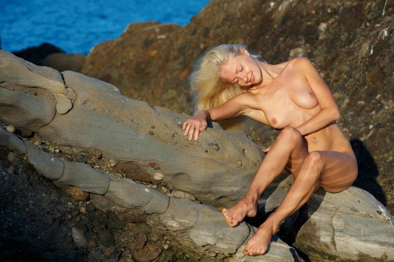 Сексапильная светлая порно звезда залезла обнаженная на прибрежные камни