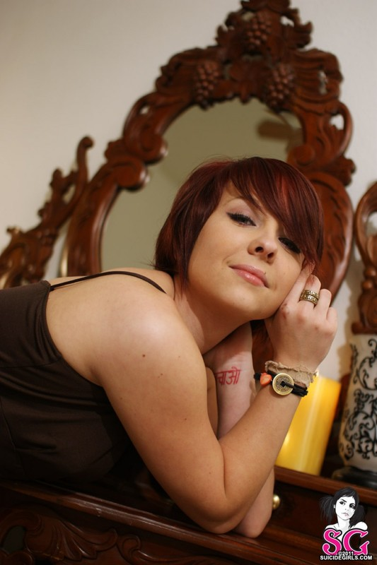 Татуированная милашка позирует возле туалетного столика