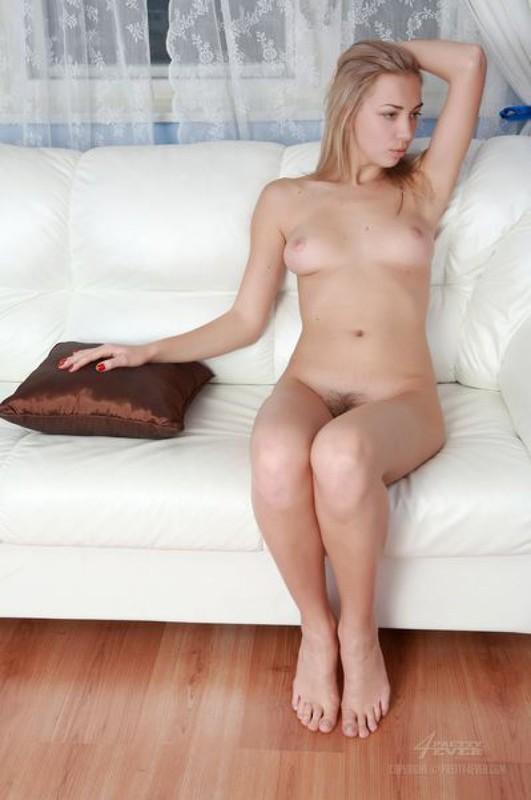 Шикарная блондиночка сидит голенькая на белом диване