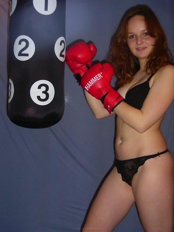 Полуголая боксерша тренируется в комнате с грушей