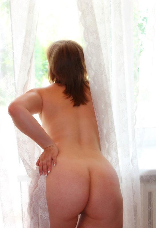 Милфа стоит рядом с окном и блистает королевской попой