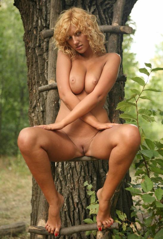 Блондинка голышом сидит на лестнице приколоченной к дереву