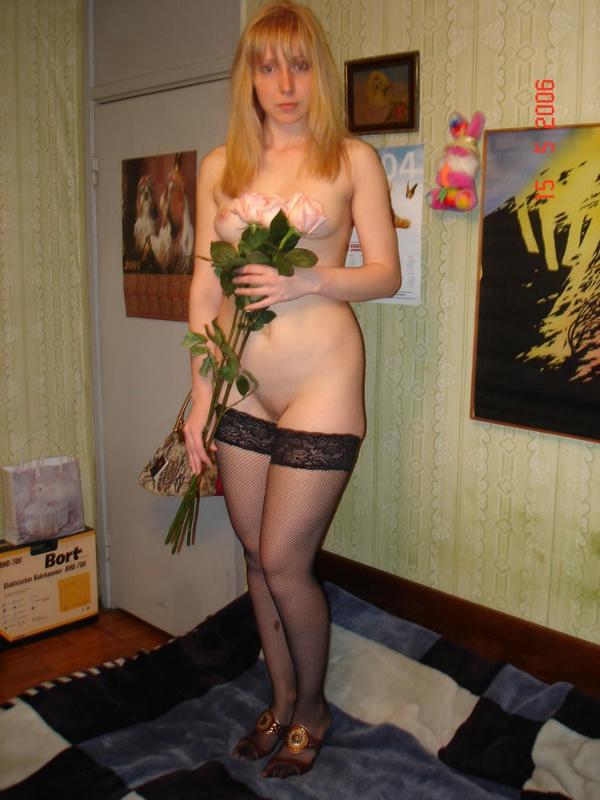 Голая мамка с цветами стоит посреди комнаты