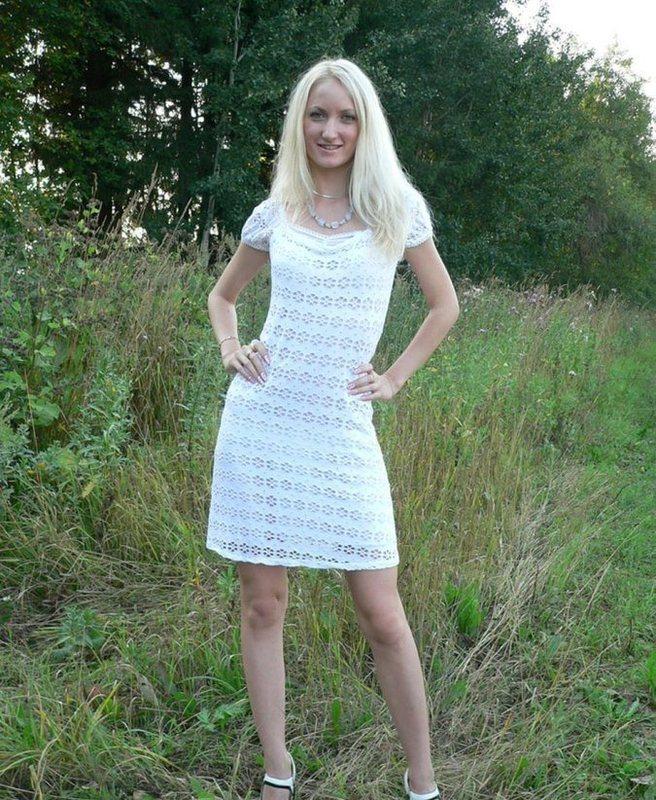 Светловолосая девушка продемонстрировала обнаженную пизду под белым платьем около растений