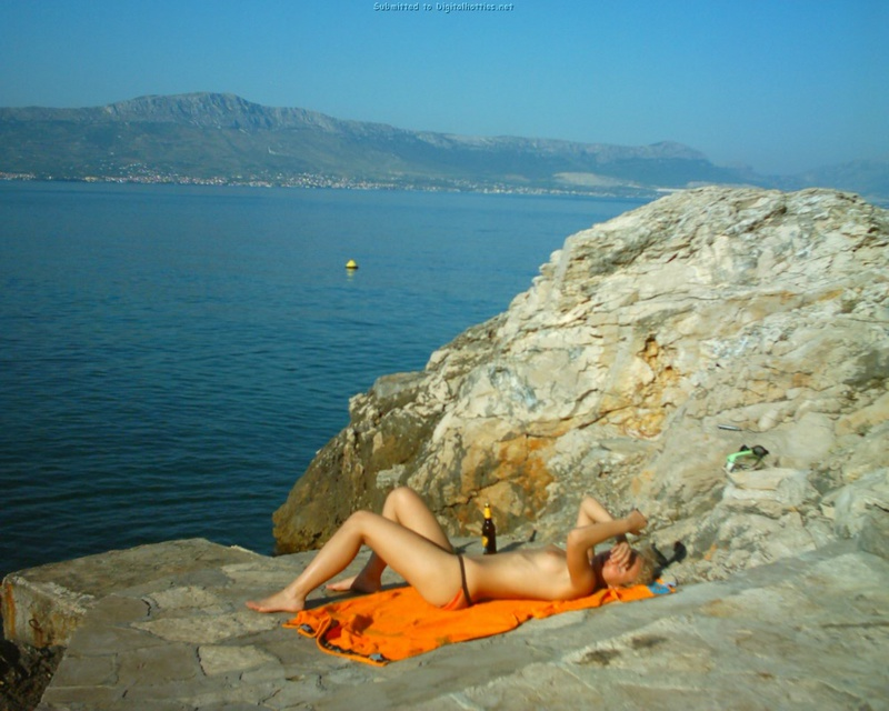 Голая бикса проводит время на скале у моря