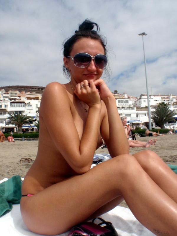 Баловница принимает солнечные ванны на общественом песке без лифчика