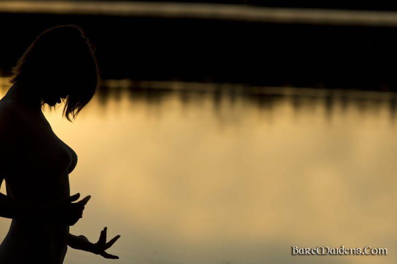 Бреа стоит недалеко от озера во время заката